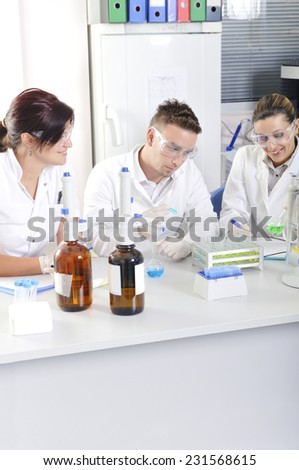 Attractive young PhD students scientists observing the blue and green indicator color shift after the solution destillation in chemical laboratory - stock photo