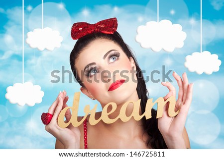 Attractive young pinup girl looking up to the clouds of inspiration with the words dream in hand. Dreaming to achieve to succeed - stock photo