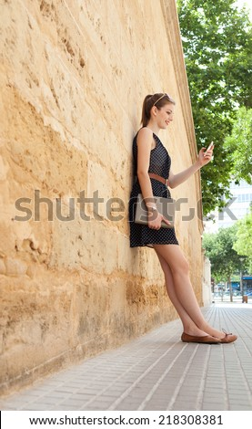 Attractive young professional business woman using a smartphone while relaxing leaning on an office building stone wall during a sunny day, outdoors. Technology and telecommunications.