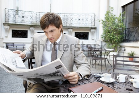 Attractive young professional reading a newspaper while having coffee in a colonial building's patio. - stock photo