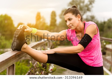 Attractive young runner woman doing stretching exercises. - stock photo