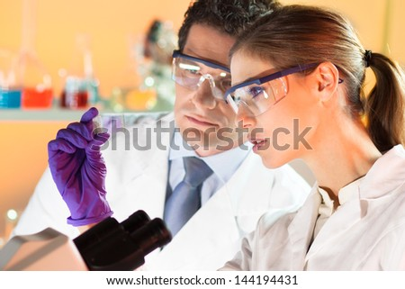 Attractive young scientist and her supervisor looking at the microscope slide in the forensic laboratory. - stock photo