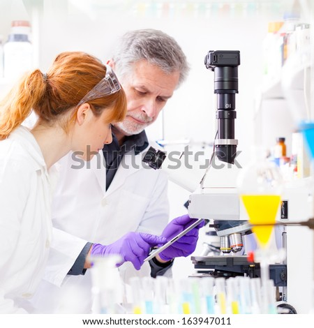 Attractive young scientist and senior male supervisor checking experiment protocol at tablet laptop computer in life science research laboratory (biochemistry, genetics, forensics, microbiology) - stock photo