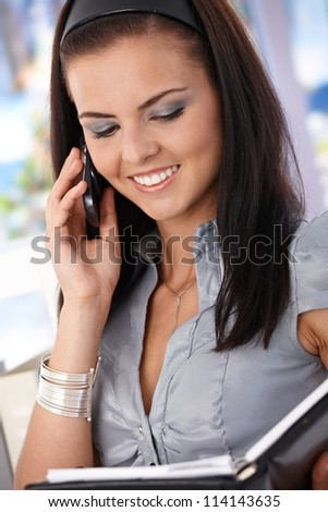 Attractive young secretary talking on mobile, looking at organizer, smiling. - stock photo