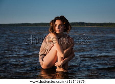 Attractive young seminude woman in a wet suit posing against the sea background