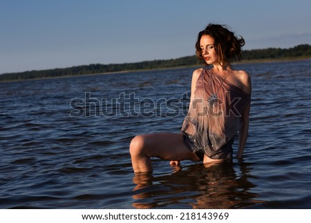 Attractive young seminude woman in a wet suit posing against the sea background. Evening light with deep shadows and color shift