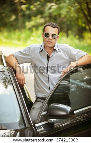 attractive young serious man standing next car sunglasses background summer green park