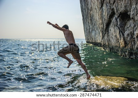 Attractive young shirtless athletic man jumping in water by sea or ocean shore, wearing shorts - stock photo