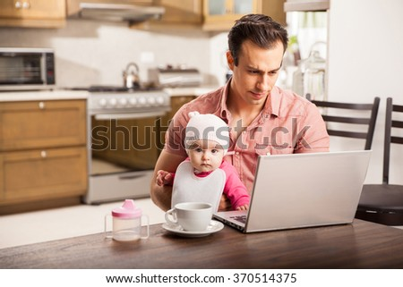 Attractive young single dad working on a laptop computer at home while taking care of his baby daughter - stock photo
