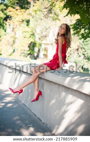 Attractive young slim woman on a city street, lady in red dress and high heels has fun, sitting, smiling - stock photo