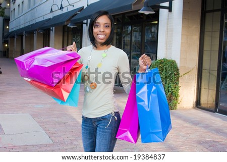 Attractive, young, smiling, African American woman with colorful shopping bags walking in an urban city environment. - stock photo
