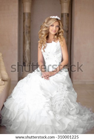 Attractive young smiling bride woman in wedding dress. Beautiful girl with curly hair style and professional bridal makeup posing in interior. - stock photo