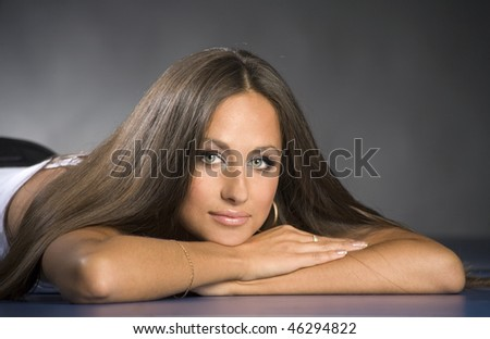 Attractive young smiling brunette girl is lying and thinking - stock photo