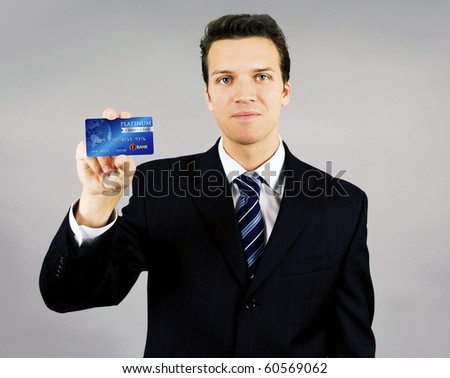 Attractive young smiling business man holding a credit card - stock photo