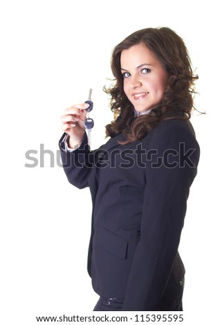 Attractive young smiling girl in a black business suit. In her right hand she holds the keys. Isolated on white background