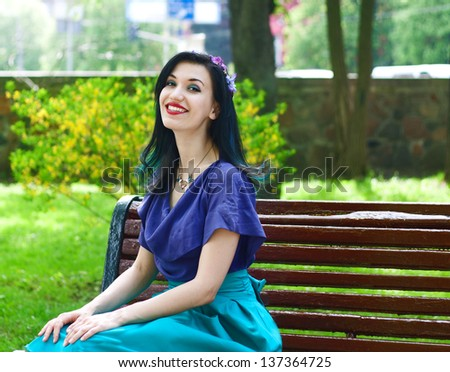 Attractive young smiling girl sitting on bench with his hands on  knees. Outdoor portrait. - stock photo