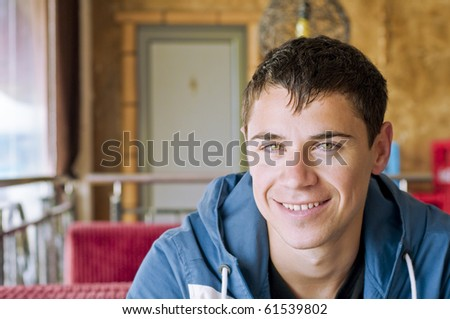 Attractive young smiling man with urban look  sitting in a cafe - stock photo