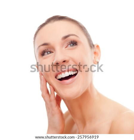 Attractive young smiling woman showing her perfect radiant skin on white background - stock photo