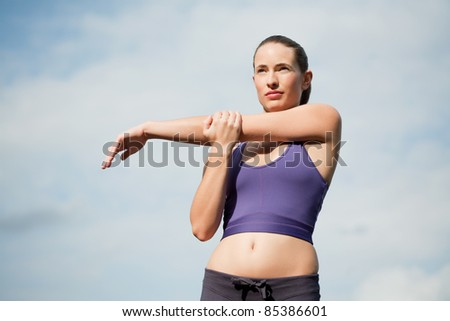 attractive young sportswoman stretching and warming up - stock photo