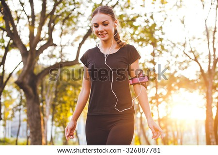 Attractive young sporty smiling woman in sportswear walks in park at sunset with armband and earphones listening to music during training - stock photo