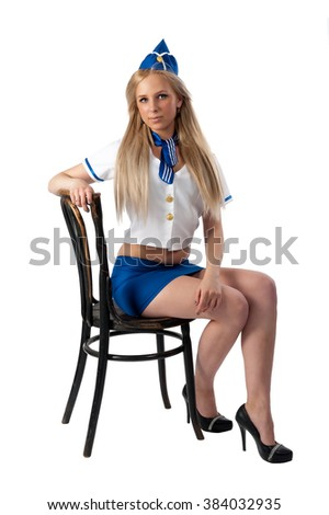 Attractive young stewardess sitting on vintage chair. Isolated over white background - stock photo
