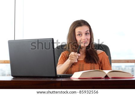 Attractive young student happily studying and looking at the camera