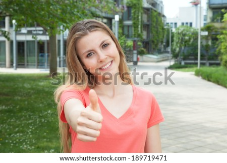 Attractive young student showing thumb up in campus - stock photo