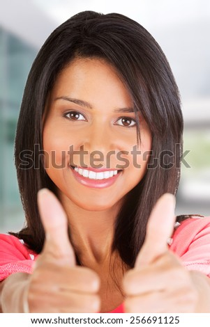 Attractive young student woman gesturing OK. - stock photo