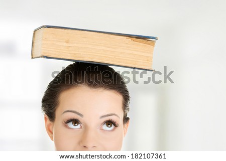 Attractive young student woman with book on head - stock photo