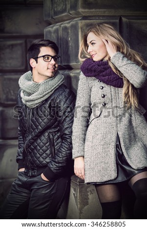 Attractive young stylish couple dressed in warm cloths standing and looking on each other outdoors - stock photo