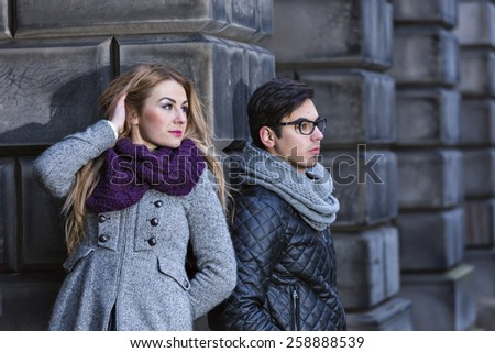 Attractive young stylish couple looking aside dressed in warm cloths outdoors  - stock photo