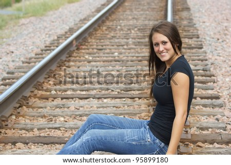 Attractive young teen girl sitting on railroad tracks - stock photo