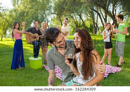 Attractive young teenage couple drinking red wine and enjoying a picnic with friends in the park as they play the guitar and dance - stock photo