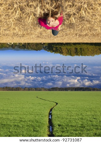 Attractive young teenage white Caucasian female floating above a beautiful field landscape with upside down clouds - stock photo