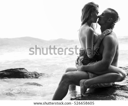 Attractive young topless couple hugging while sitting on the rock by the sea over sky background - black and white photo