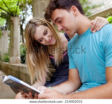 Attractive young tourist couple sitting down on a  wooden bench while visiting a green garden park on a weekend city travel break, reading a guide book and enjoying a summer holiday outdoors. - stock photo