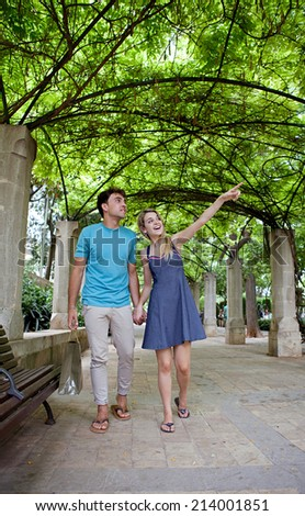 Attractive young tourist couple visiting a green garden park on a weekend city travel break, pointing at monumental sights. Loving girlfriend and boyfriend enjoying a summer holiday outdoors. - stock photo