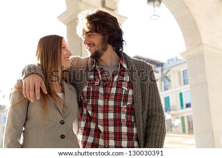 Attractive young tourist couple with arms around each other while visiting a destination city on vacation during a sunny morning.