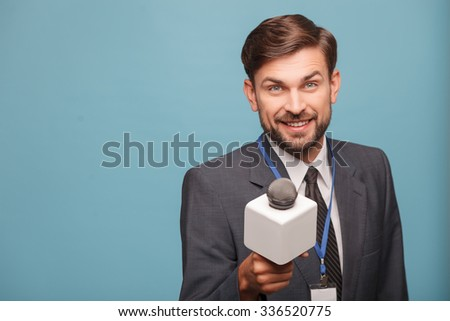 Attractive young tv journalist is interviewing someone with joy. He is standing and stretching a microphone forward. The man is looking at camera and smiling. Isolated and copy space in left side - stock photo