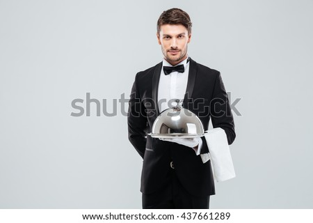 Attractive young waiter in tuxedo holding serving tray with metal cloche and napkin - stock photo