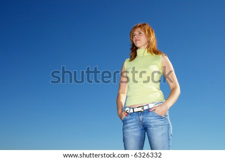 attractive young woman against blue sky - stock photo