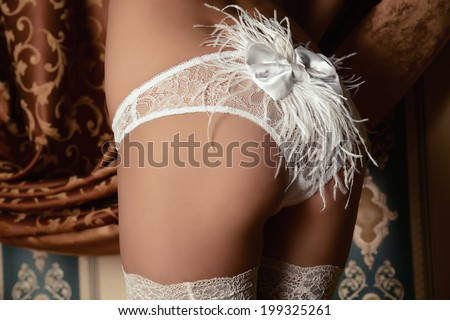 Attractive young woman alluring in sexual white lingerie. - stock photo