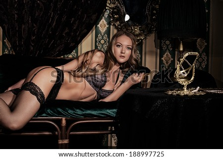 Attractive young woman alluring in sexy lingerie. Vintage interior.  - stock photo