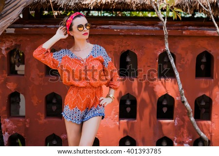 Attractive young woman among the Asian wall. Vacation. Tropics. Fashion shot. - stock photo