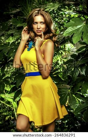 Attractive young woman  among the tropical plants. Vacation. Tropics. Fashion shot. - stock photo