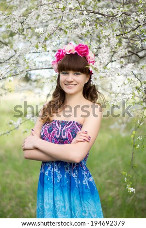 Attractive young woman and blooming tree in garden