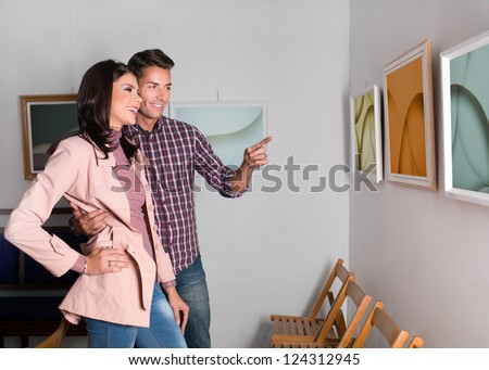 attractive young woman and man at a photography exhibition enjoying themselves, laughing, hugging and pointing at one of the  works