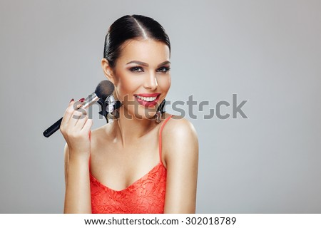 Attractive young woman applying blush - stock photo