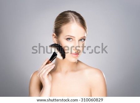 Attractive young woman applying powder on her cheeks. - stock photo