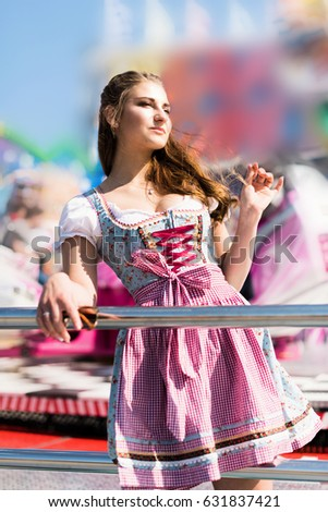 Attractive young woman at German funfair Oktoberfest with traditional dirndl dress and joyride in the background